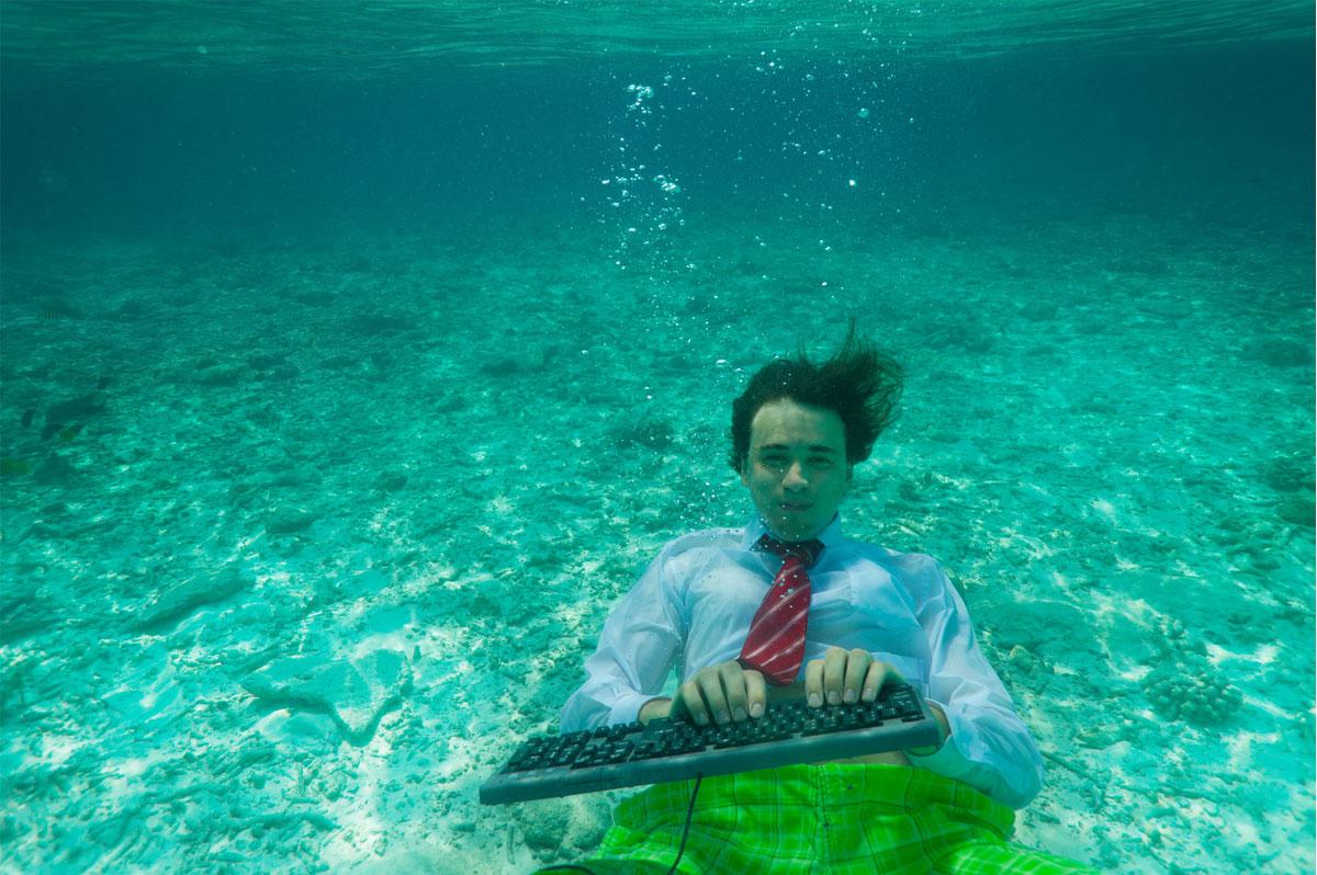 Un homme d'affaires tape sur son clavier... sous l'eau !