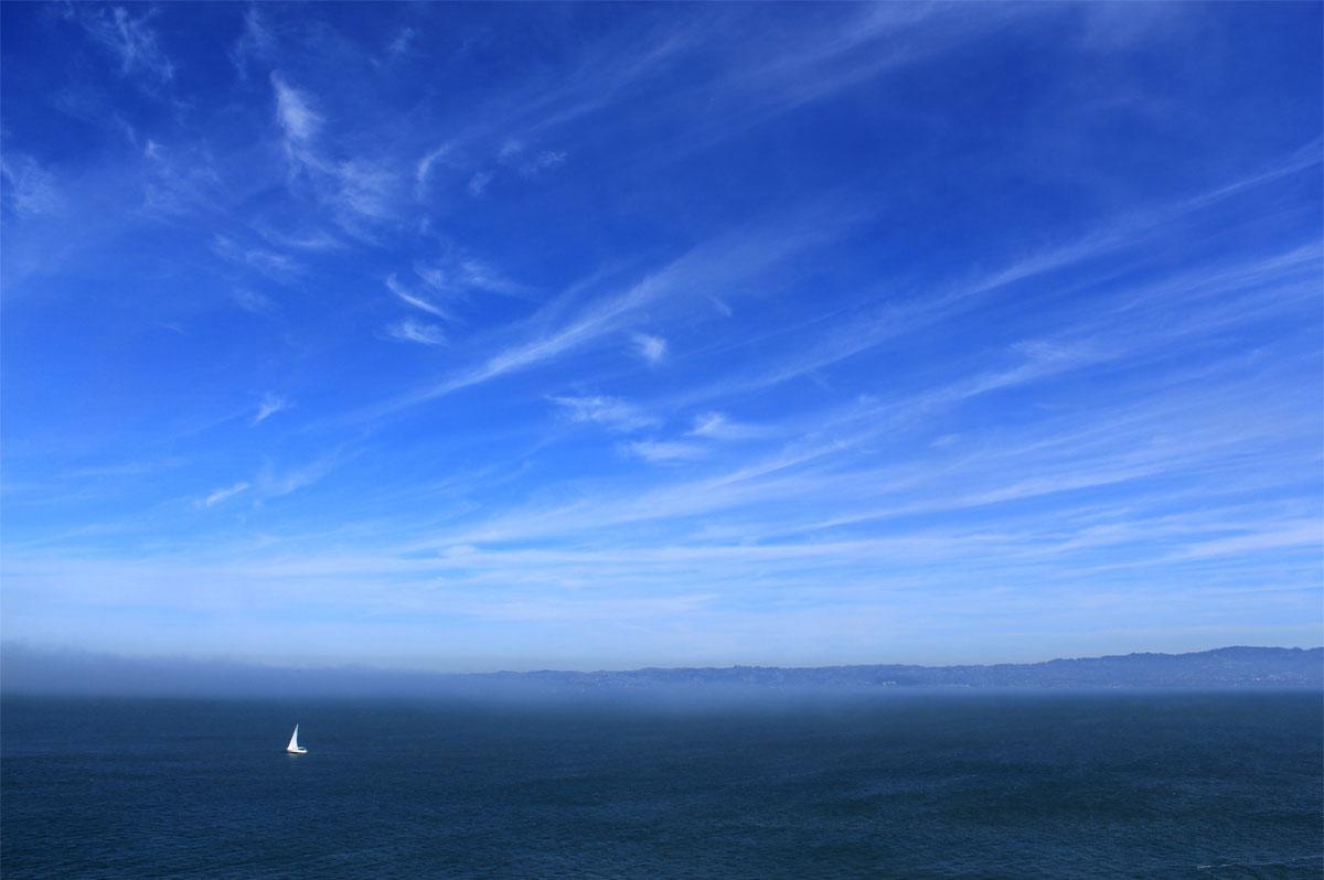 Voilier blanc dans l'immensité de l'océan, avec des terres à l'horizon