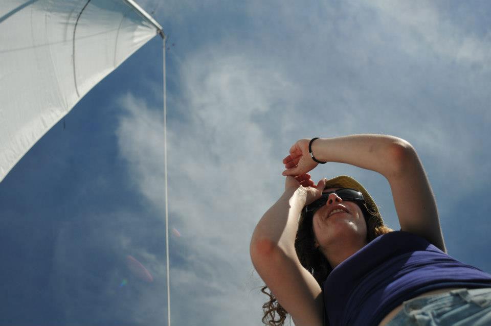 Sur un voilier, une femme regarde à l'horizon